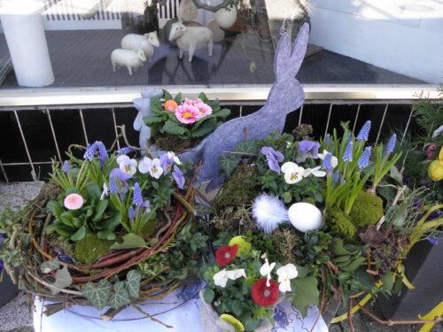 Blumengestecke in Körben sind mit Zweigen , primeln und Gänseblümchen dekoriert. In der Mitte sitz ein Osterhase aus Filz.