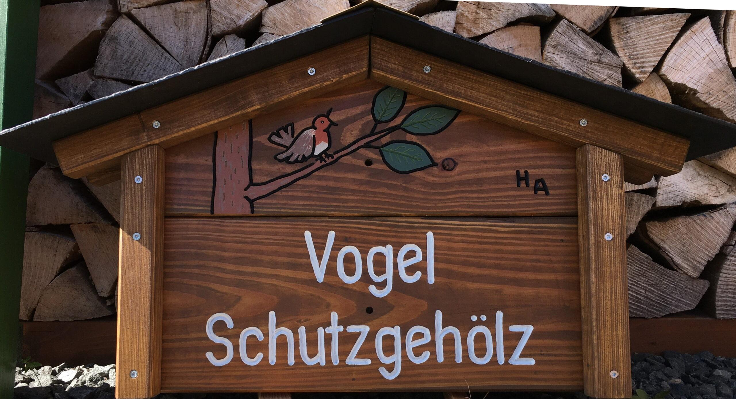 ein selbstgeschnitztes Holzschild zeigt einen Singvogel auf einem Ast Darunter steht in weißer Druckschrift VOGEL SCHUTZGEHÖLZ. Ein kleines Dach schützt das Schild gegen Verwitterung