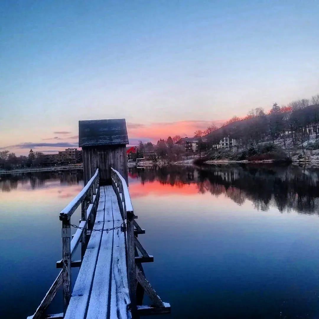 Der Steg eines Striegelhauses vor einem spiegelglatten Teich in Blau-Rot-Tönen zur Zeit der Abenddämmerung, der sog. Blauen Stunde