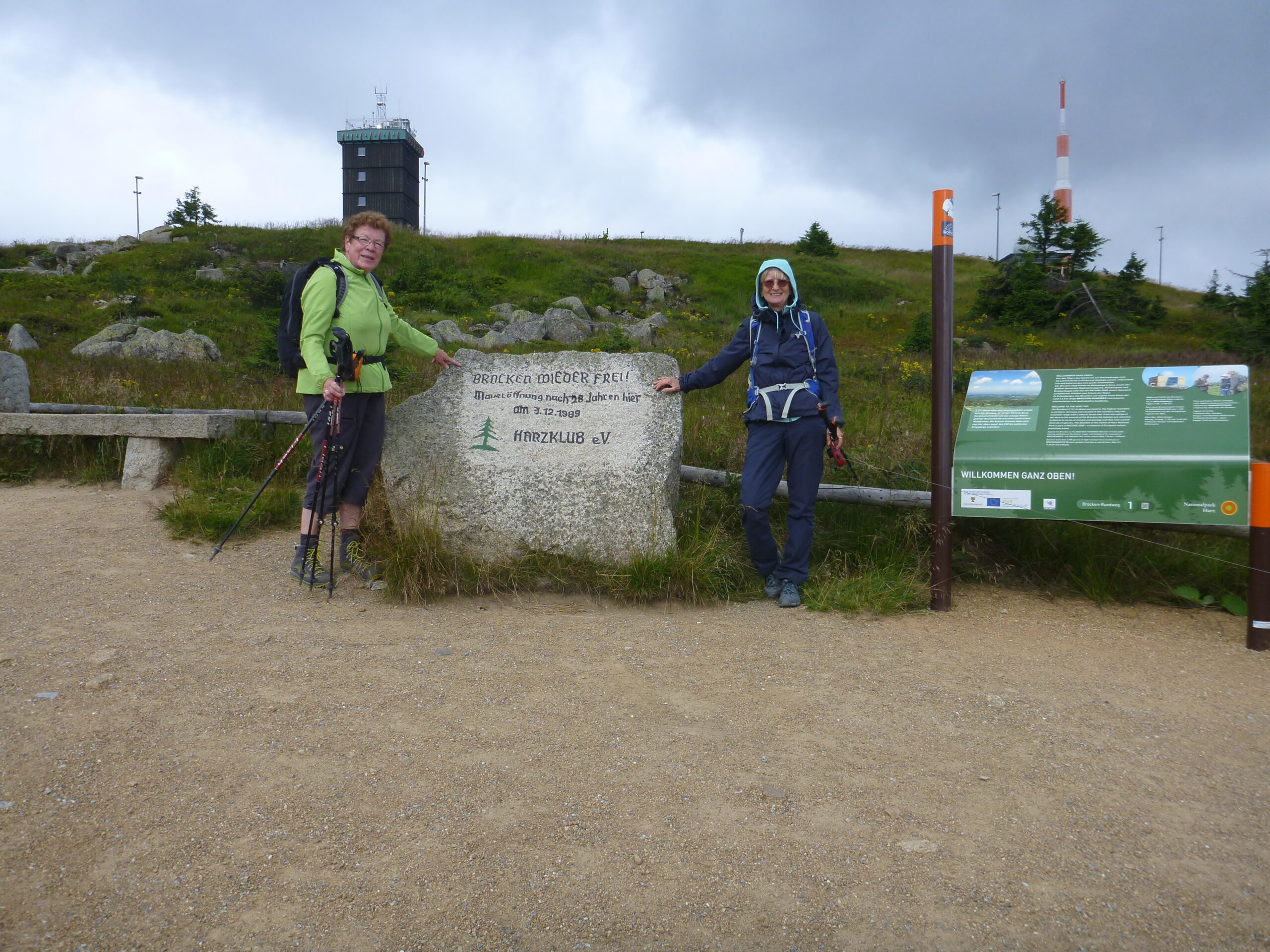 2 Wanderinnen stehen neben einem Gedenkstein mit der Inschrift: Brocken wieder frei