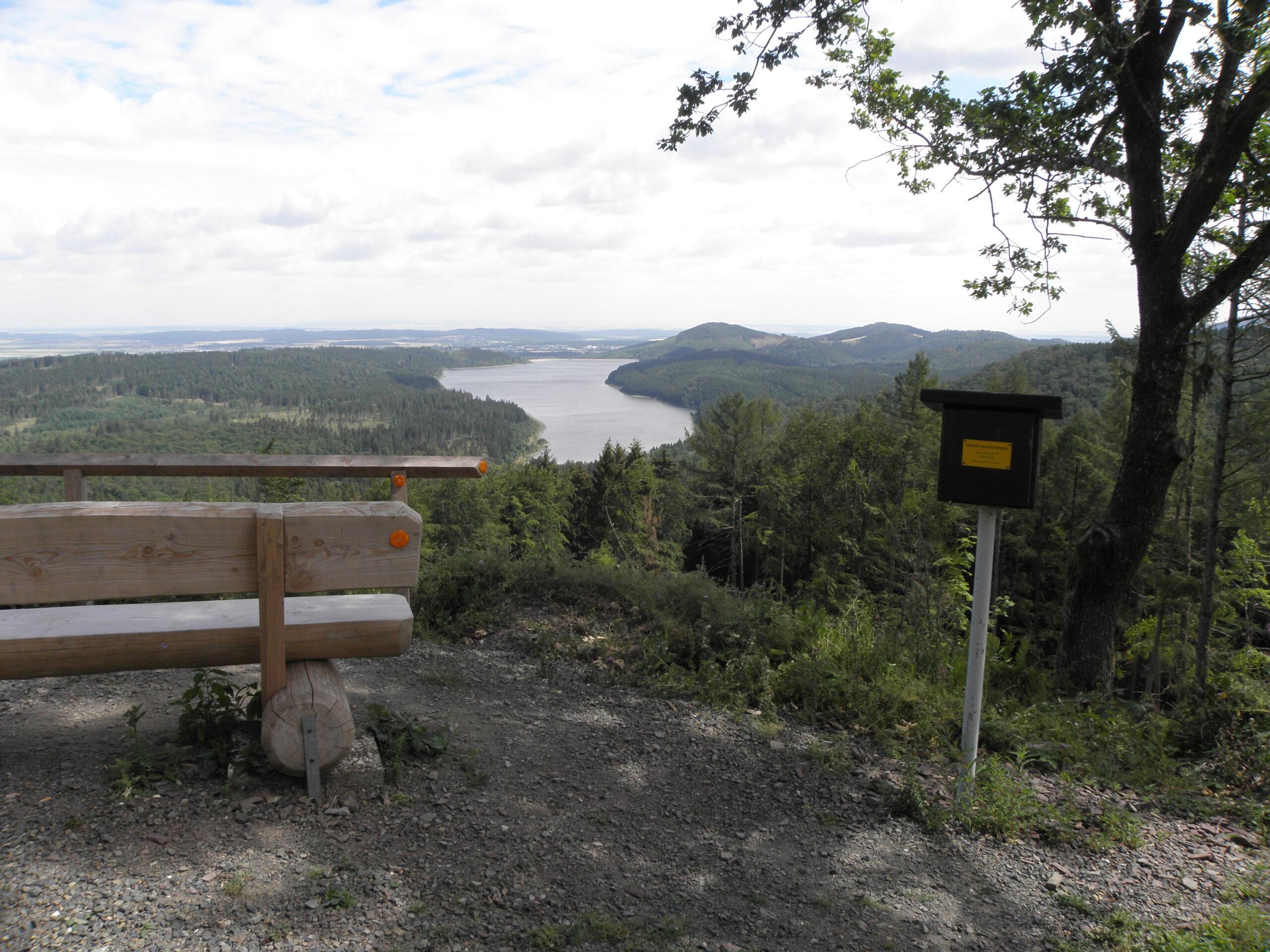 Neben einer rustikalen Holzbank steht ein grüner Kasten. Dies ist ein Stempelkasten für die Harzer Wandernadel.Der Wanderer geniesst einen weiten, freien Blick über einen Seitenarm der Granatalsperre nach Norden in das Harzvorland.